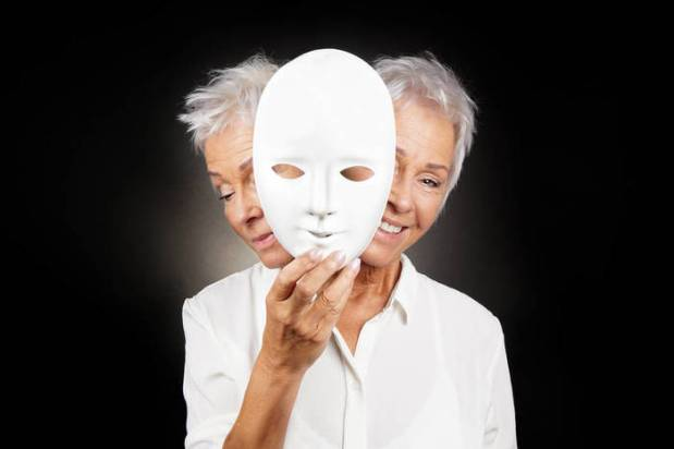 older woman hiding happy and sad face behind mask
